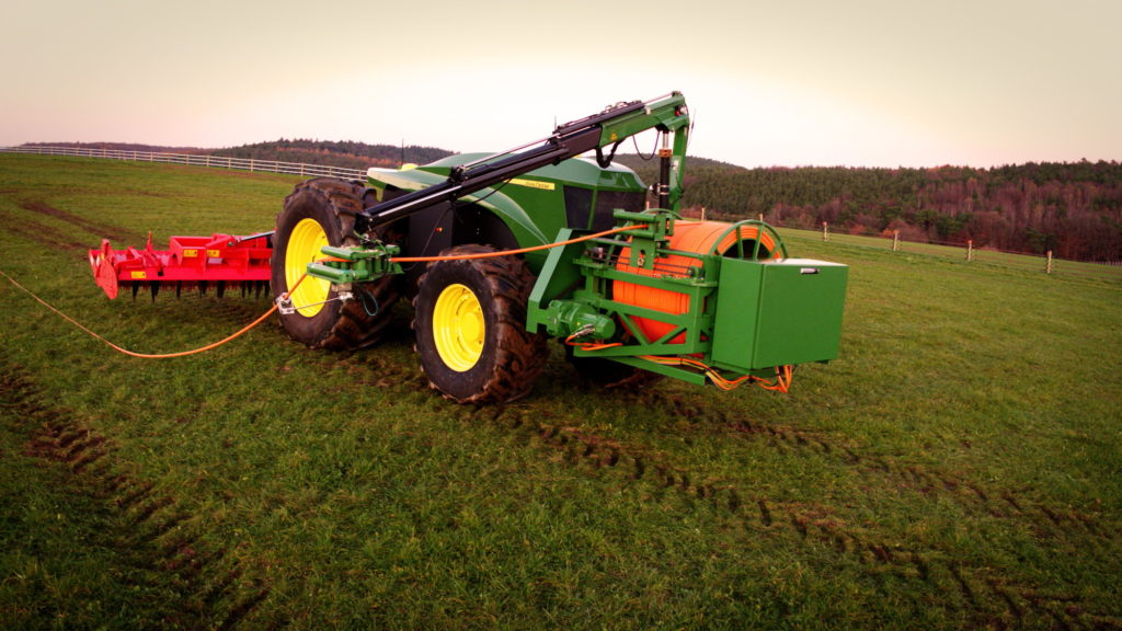 Traktor mit Stromkabel auf dem Acker