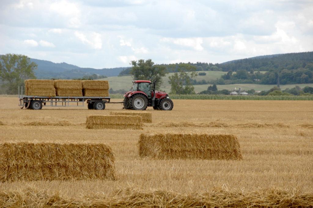 Ein Traktor fährt Stroh von einem Acker