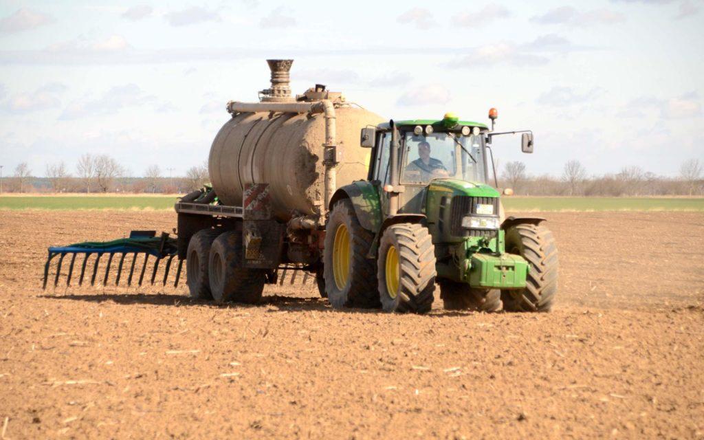 Traktor bringt Dünger auf den Acker aus