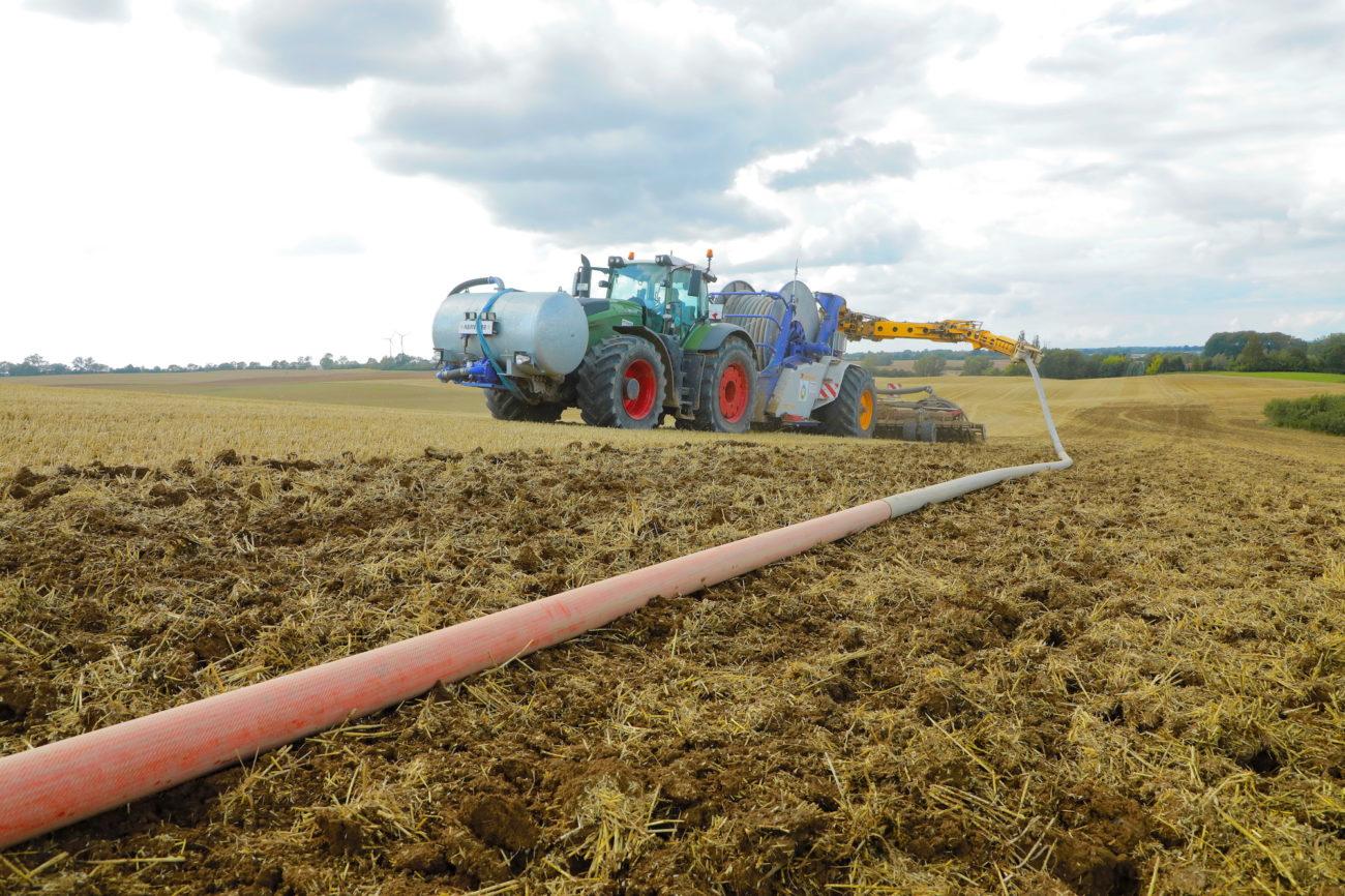 Traktor beim Gülle ausbringen mit dem Schlauch