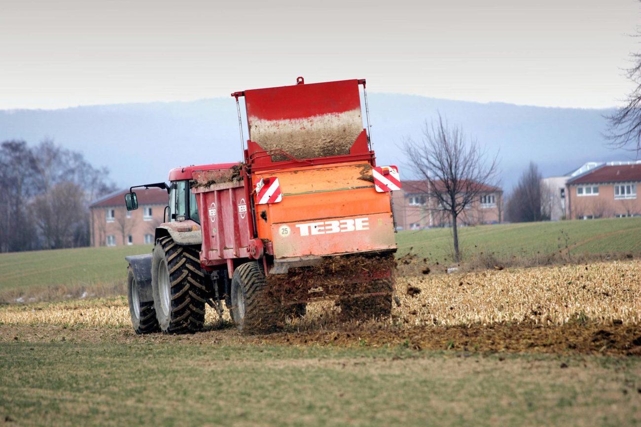 Traktor streut Mist auf einem Feld in Elze - Niedersachsen