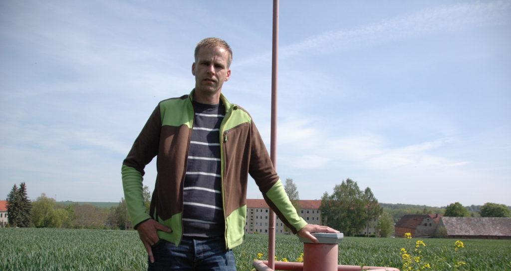 """An der Messstelle in seiner Flur, die den Nitratüberschuss belegen soll: Pflanzenbauchef Denis Fischer. Rings um Rositz finden sich Dutzende Messstellen, auch auf Äckern – im rechten Bild mit Blick auf die berühmt-berüchtigte """"Neue Sorge"""" in Rositz."""