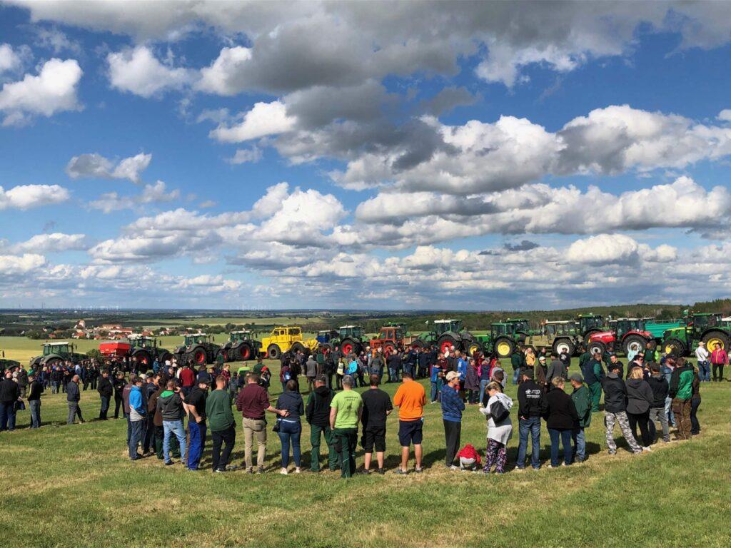 Menschen stehen auf einer grünen Wiese, am blauen Himmel sind Wolken, der Blick schweift ins Land.