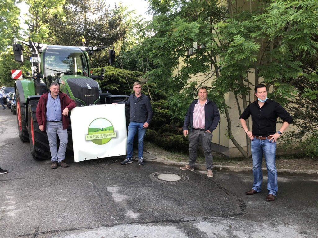 Gero Hocker und drei weitere Männer stehen vor einem Traktor, an dessen Front ein Transparent der Organisation LsV Sachsen befestigt ist