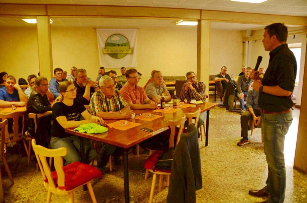 Der FDP-Abgeordnete Gero Hocker steht rechts im Bild vor einer Gruppe sitzender Landwirte. Im Hintergrund ist das sächsische LsV-Logo an der Wand befestigt.
