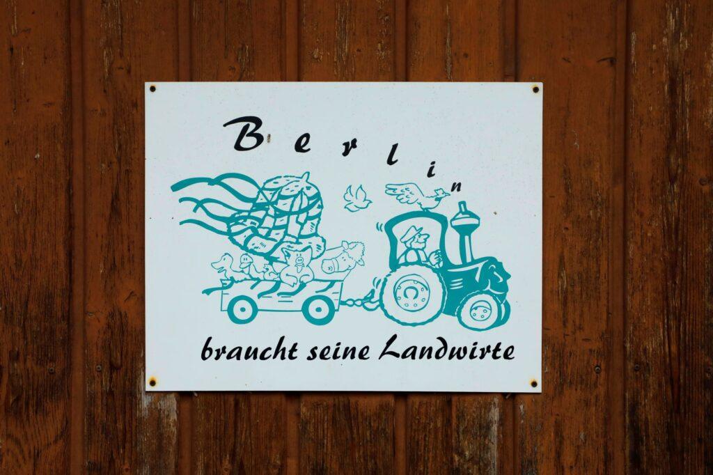 """Schild mit Aufschrift: """"Berlin braucht seine Landwirte""""."""