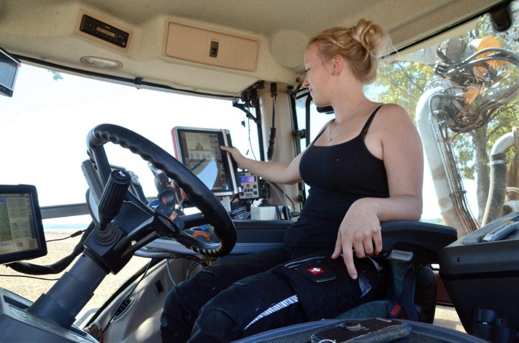 Eine junge Frau sitzt in der Fahrerkabine eines Traktors und tippt mit den Fingern auf einen Bildschirm. Das Ausbringen der Gülle dient der Vorbereitung der Aussaat.