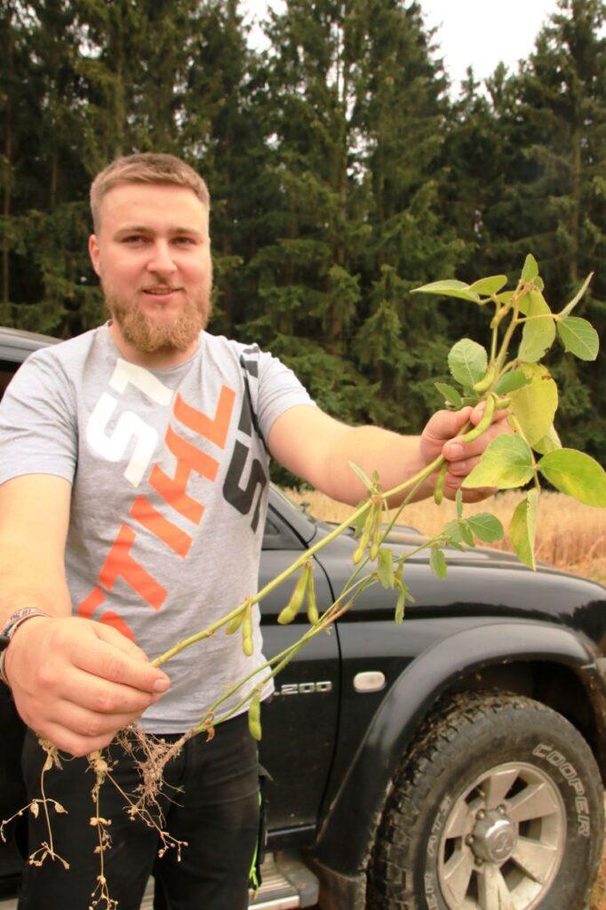 Joahnn Singer zeigt eine Sojapflanze von seinem Schlag.