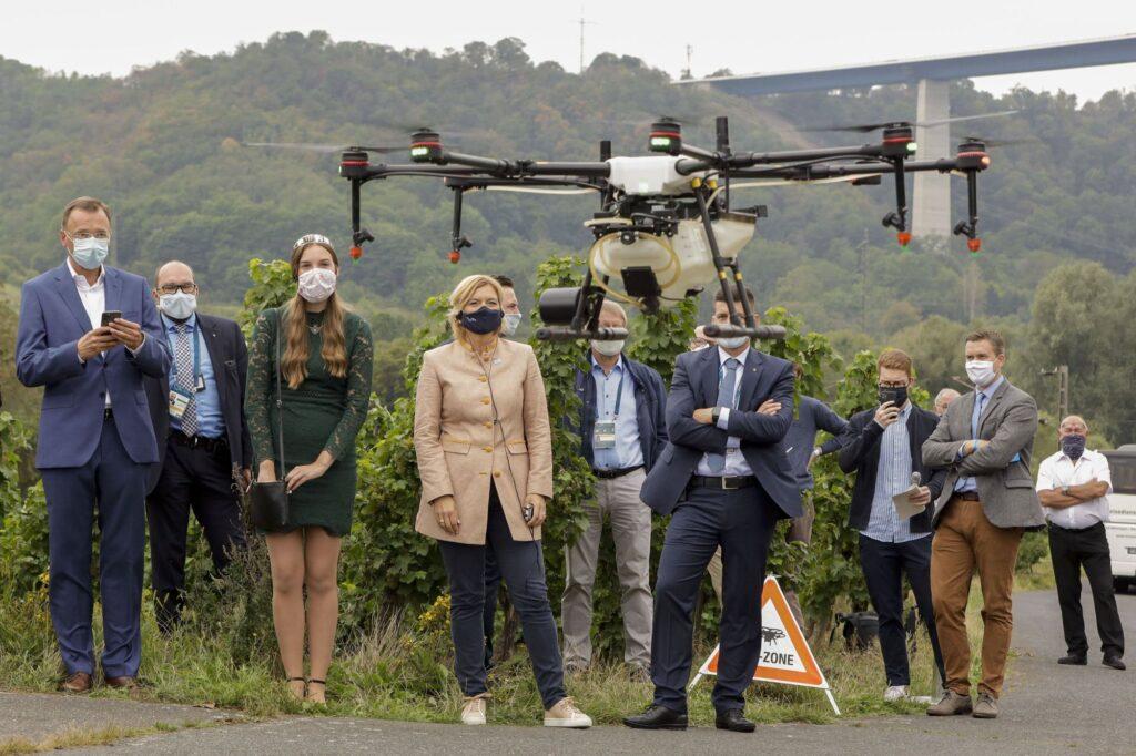 Agrarministerin Julia Klöckner und EU-Kollegen bei der Vorführung einer Drohne für Pflanzenschutz.