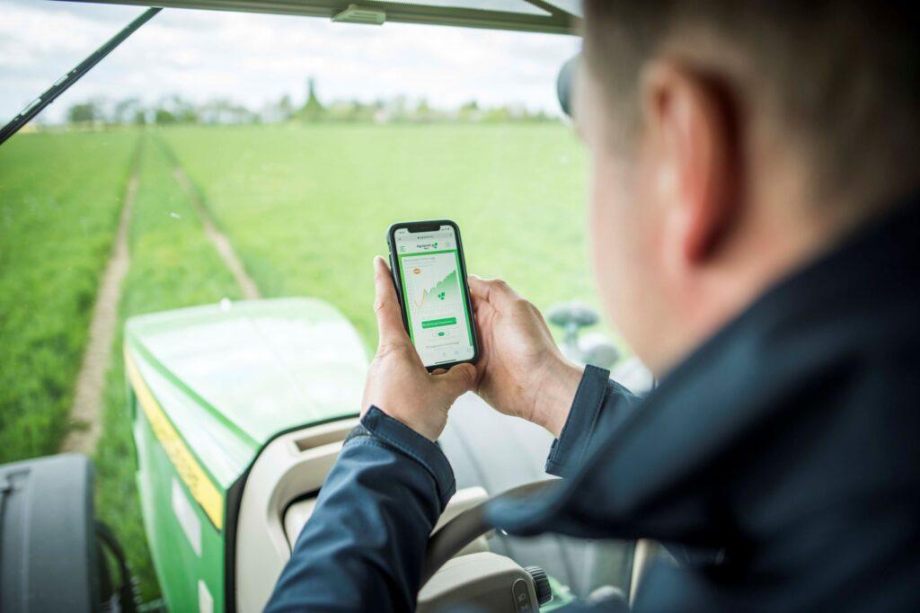 Ein Landwirt sitzt in seinem Traktor und schaut auf sein Smartphone, im Hintergrund sieht man ein Getreidefeld