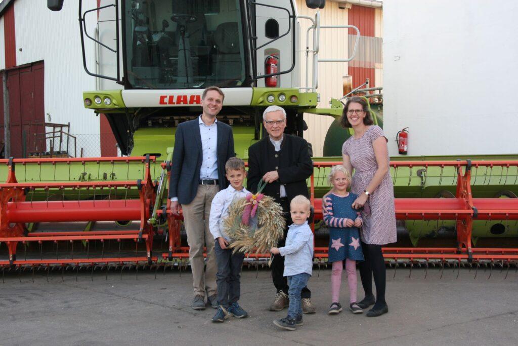 Familie Große Rüschkamp hält mit Erzbischof Heiner Koch einen Erntekranz, hinter ihnen steht ein Mähdrescher.